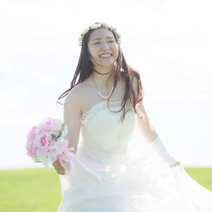 草原でブーケを持ち微笑む花嫁の写真素材 [FYI01968464]