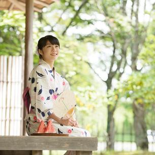 縁側に座り微笑む浴衣姿の女性の写真素材 [FYI01969017]