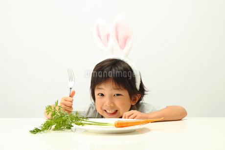 お皿に置かれたニンジンとうさぎの耳を付けた男の子の写真素材 [FYI01969128]