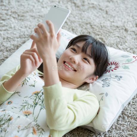 床に寝転びスマートフォンを見る女性の写真素材 [FYI01969224]