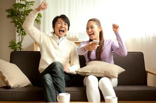 スマートフォンでリモコン操作をしてテレビを見る夫婦の写真素材 [FYI01969374]