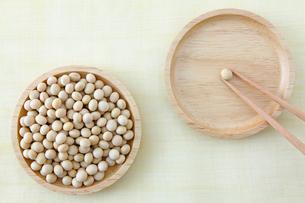 大豆が入った木の器と大豆をつまむ箸の写真素材 [FYI01970175]