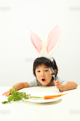 お皿に置かれたニンジンとうさぎの耳を付けた男の子の写真素材 [FYI01970363]