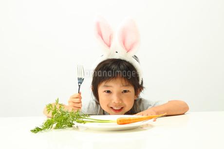 お皿に置かれたニンジンとうさぎの耳を付けた男の子の写真素材 [FYI01970915]
