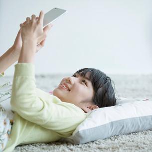 床に寝転びスマートフォンを見る女性の写真素材 [FYI01970919]