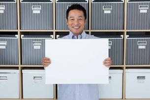 棚の前に立ってホワイトボードを持つ日本人男性の写真素材 [FYI01971541]