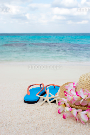 砂浜に置かれた麦わら帽子とビーチサンダルの写真素材 [FYI01972813]