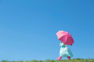 レインコートを着てピンクの傘をさして歩く女の子の写真素材 [FYI01973020]