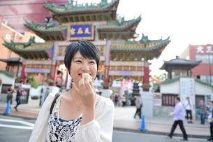 中華街で肉まんを食べてる女性の写真素材 [FYI01973064]