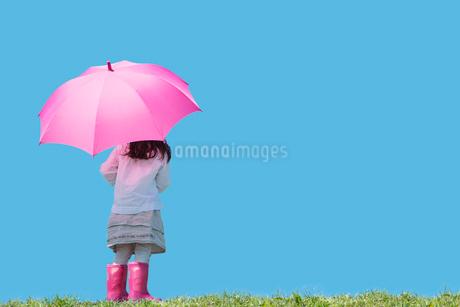 ピンクの傘と長靴の女の子の後ろ姿の写真素材 [FYI01973498]