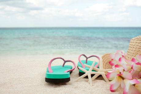砂浜に置かれた麦わら帽子とビーチサンダルの写真素材 [FYI01973648]