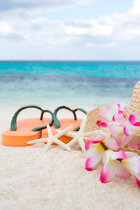 砂浜に置かれた麦わら帽子とビーチサンダルの写真素材 [FYI01974585]