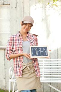 OPENのボードを持つカフェ店員の写真素材 [FYI01974612]