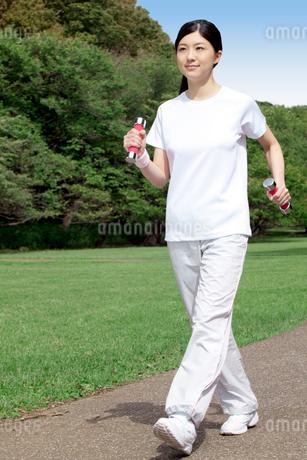 ダンベルを持ってウォーキングする女性の写真素材 [FYI01974763]