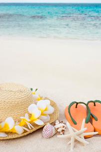 砂浜に置かれた麦わら帽子とビーチサンダルの写真素材 [FYI01974840]