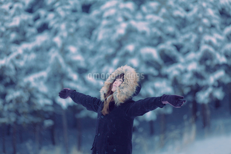 雪が積もった森で手を広げて立つ女性の写真素材 [FYI01975333]
