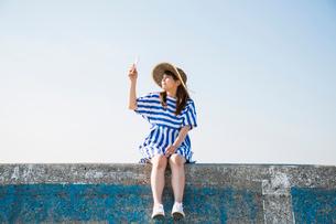 堤防に座ってスマートフォンで撮影する女性の写真素材 [FYI01975747]