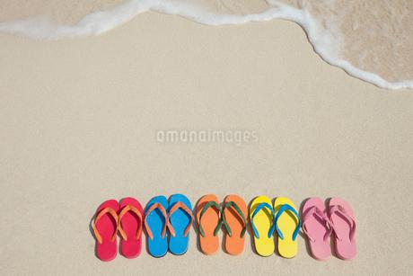 波打ち際に並べられたビーチサンダルの写真素材 [FYI01976073]