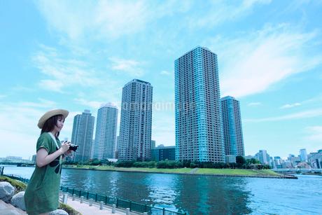 川沿いでカメラを持つ若い女性の写真素材 [FYI01976124]