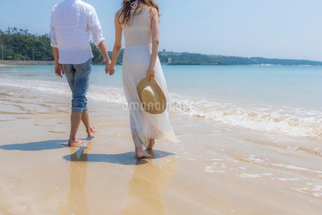 波打ち際を歩くカップルの後姿の写真素材 [FYI01976396]