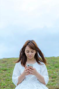 草原に座ってスマートフォンを見る女性の写真素材 [FYI01977327]
