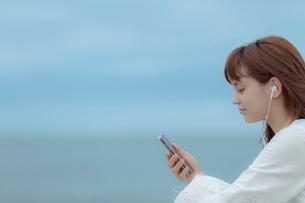 スマートフォンで音楽を聴く女性の写真素材 [FYI01977540]