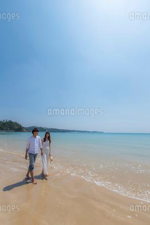 波打ち際を歩くカップルの写真素材 [FYI01977594]
