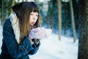 雪に息を吹きかけて飛ばす女性の写真素材 [FYI01977939]