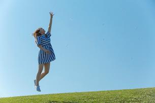 草原をジャンプする女性の写真素材 [FYI01978084]