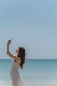 海辺でスマートフォンで撮影する女性の写真素材 [FYI01978107]