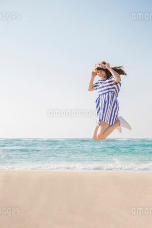 砂浜でジャンプする女性の写真素材 [FYI01978178]