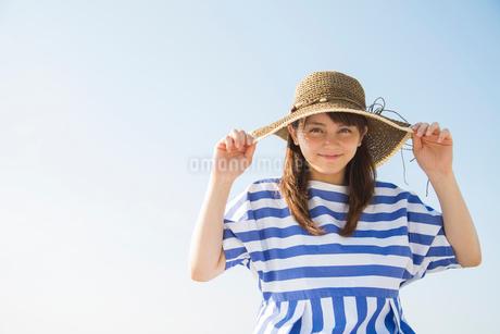 青空と麦わら帽子をかぶった笑顔の女性の写真素材 [FYI01978194]