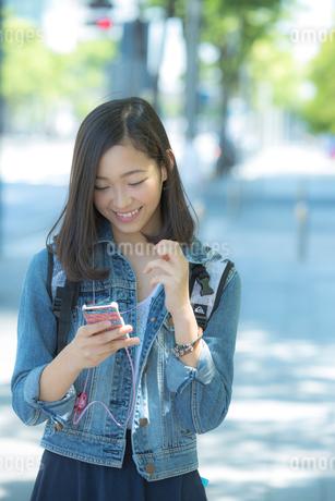 スマートフォンで音楽を聴く女性の写真素材 [FYI01978439]