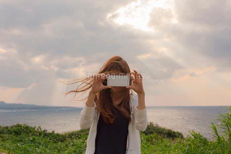 海辺でスマートフォンで撮影する女性の写真素材 [FYI01978848]