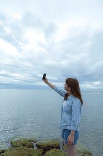 海岸に立ってスマートフォンで自分を撮影する女性の写真素材 [FYI01979189]