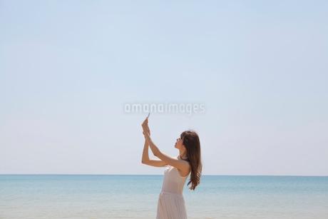 海辺でスマートフォンで撮影する女性の写真素材 [FYI01979386]