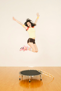 Woman in midair jumping on trampolineの写真素材 [FYI01980424]