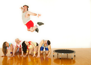 Man jumping over a line of other peopleの写真素材 [FYI01980440]