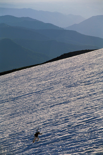 View of skier carrying skis up mountainの写真素材 [FYI01980931]