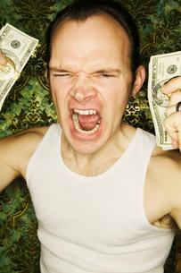 Shouting man holding dollar billsの写真素材 [FYI01982320]