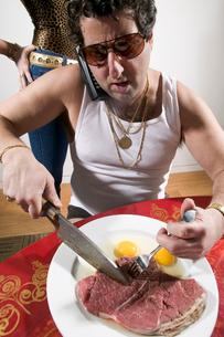 Man eating raw steak and eggsの写真素材 [FYI01982369]