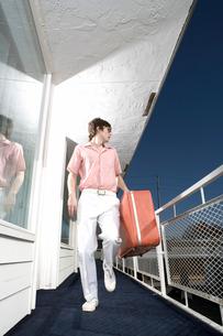 Man carrying suitcase on motel balconyの写真素材 [FYI01982790]