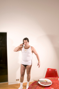 Man in underwear talking on cell phoneの写真素材 [FYI01983020]