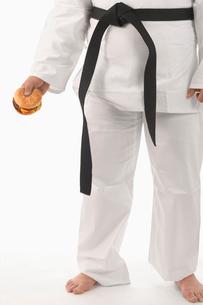 Man in karate outfit eating burgerの写真素材 [FYI01983038]
