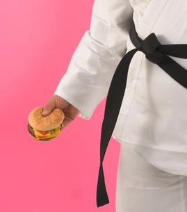 Man in karate outfit eating hamburgerの写真素材 [FYI01983073]