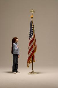 Young girl saluting American flagの写真素材 [FYI01983084]