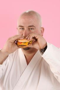 Man in karate outfit eating hamburgerの写真素材 [FYI01983097]