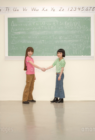 Young girls shaking hands in classroomの写真素材 [FYI01983153]