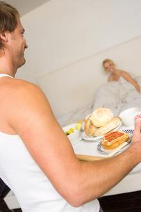 Man bringing wife breakfast in bedの写真素材 [FYI01983321]