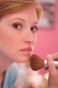 Young woman applying makeupの写真素材 [FYI01983349]
